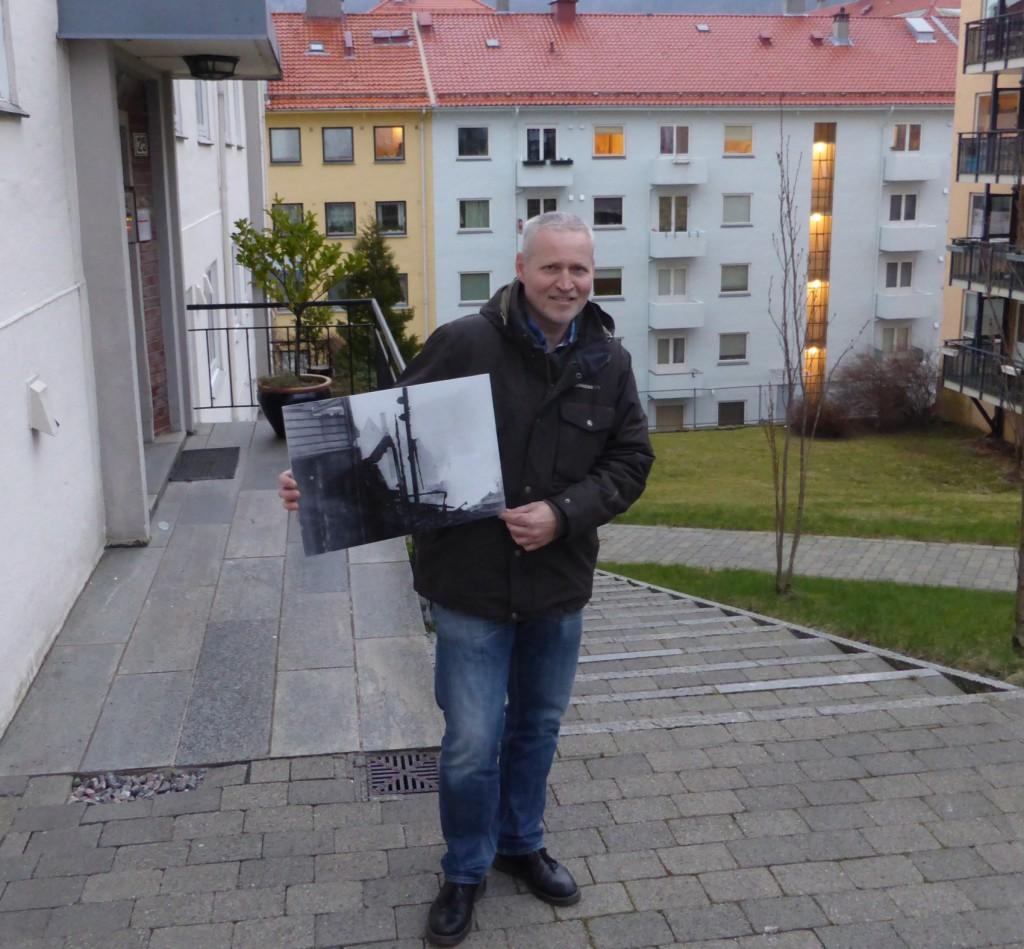 Her står Knut Georg Flo akkurat der hvor Madsenssmauet var før eksplosjonen i 1944. Han holder et bilde fra Riksarkivet på hvordan det så ut etter eksplosjonen. Foto: Eva Johansen