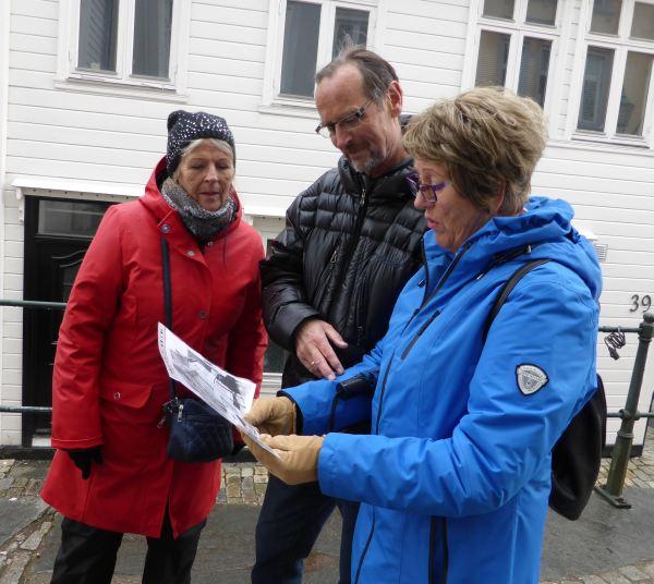 Wenche Grotli og ekteparet Rolf Hove og Torunn Hove ser på gamle bilder av de samme stedene de er på. Foto: Eva Johansen