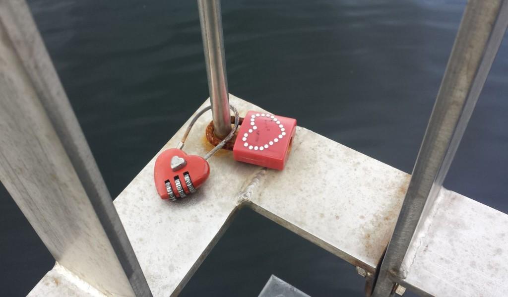 To røde hengelåser er festet til gjerdet ytterst på Ballastbryggen. Foto: Eva Johansen