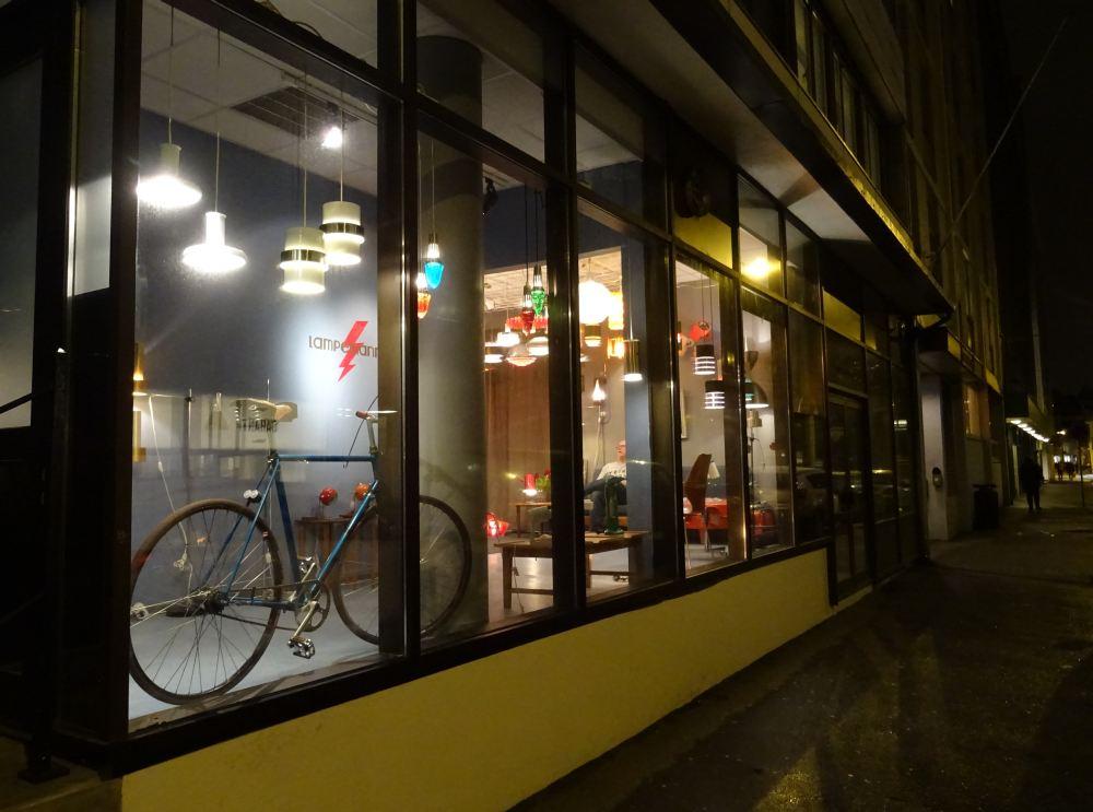 Lokalene lyser godt opp i den mørke gaten. I vinduet står en sykkel Flemming har montert selv.
