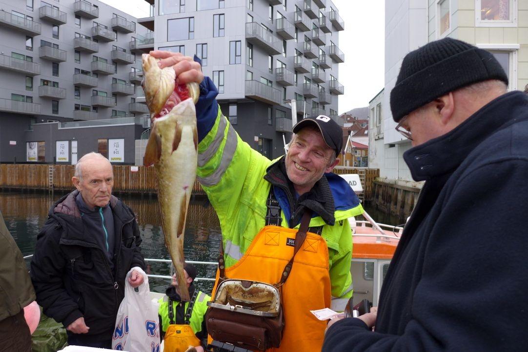 Fisker Stein Forland betjener en lang kø av bergensere som vil ha blodfersk torsk og krabbe. Kaisalg i Bergen er blitt lovlig. Foto: Ole Erik Klokeide